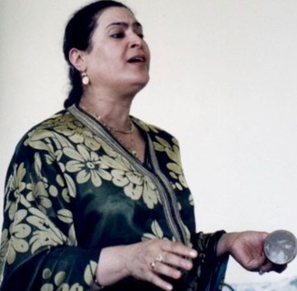 A woman holds a bell and sings.
