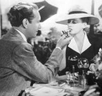 A glamorous woman's cigarette is lit by a dashing man in a suit.