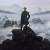 A young man dressed in a long coat looks out over a sea of fog.